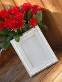 Άσπρες πλαίσιο και δέσμη των κόκκινων τριαντάφυλλων Στοκ Εικόνες