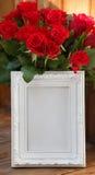 Άσπρες πλαίσιο και δέσμη των κόκκινων τριαντάφυλλων Στοκ Φωτογραφίες
