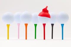 Άσπρες σφαίρες γκολφ με την αστεία ΚΑΠ Αστεία έννοια γκολφ Στοκ Εικόνα