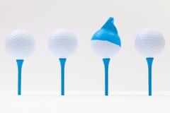 Άσπρες σφαίρες γκολφ με την αστεία ΚΑΠ Αστεία έννοια γκολφ Στοκ Εικόνες