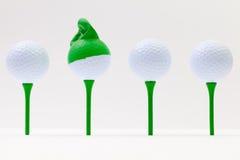 Άσπρες σφαίρες γκολφ με την αστεία ΚΑΠ Αστεία έννοια γκολφ Στοκ Φωτογραφίες