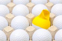 Άσπρες σφαίρες γκολφ στο κιβώτιο για τα αυγά Σφαίρα γκολφ με την αστεία ΚΑΠ Στοκ Εικόνα