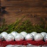 Άσπρες σφαίρες Χριστουγέννων και κόκκινες χάντρες με ξύλινο Στοκ Φωτογραφία