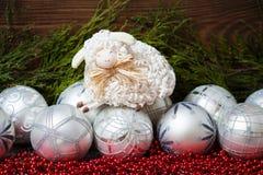 Άσπρες σφαίρες Χριστουγέννων και συμπαθητικά πρόβατα με ξύλινο Στοκ εικόνα με δικαίωμα ελεύθερης χρήσης