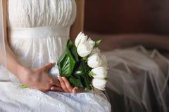 Άσπρες τουλίπες στα χέρια της νύφης Στοκ Εικόνες
