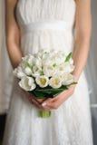Άσπρες τουλίπες στα χέρια της νύφης Στοκ Φωτογραφία