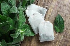 Άσπρες τσάντες τσαγιού με τα φύλλα μεντών Στοκ εικόνα με δικαίωμα ελεύθερης χρήσης