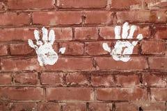 Άσπρες τυπωμένες ύλες των παλαμών των χεριών στο τουβλότοιχο στοκ εικόνες με δικαίωμα ελεύθερης χρήσης