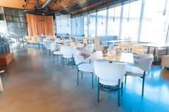 Άσπρες comfy πολυθρόνες που στέκονται κοντά στους ξύλινους πίνακες στο εστιατόριο στοκ εικόνες με δικαίωμα ελεύθερης χρήσης