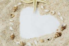 Άσπρη άμμος και διαμορφωμένο κοχύλια σύμβολο καρδιών στοκ εικόνες