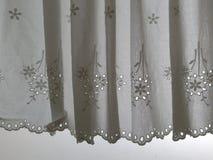 Άσπρη ένωση κουρτινών σατέν δαντελλών σκιαγραφιών στο παράθυρο με ημιδιάφανο πίσω φωτός του ήλιου, εσωτερικό δωμάτιο διακοσμήσεων Στοκ Φωτογραφία