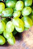 Άσπρη δέσμη σταφυλιών κρασιού πέρα από το ξύλινο υπόβαθρο Πράσινα σταφύλια macr Στοκ Φωτογραφίες