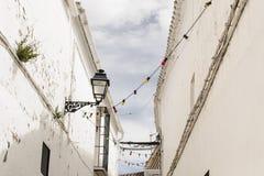 Άσπρη ανδαλουσιακή του χωριού οδός με τα ζωηρόχρωμα lightbulbs στοκ εικόνα