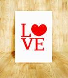 Άσπρη αφίσα με τη λέξη αγάπης στο ξύλινο δωμάτιο παρκέ, βαλεντίνος συμπυκνωμένος Στοκ φωτογραφία με δικαίωμα ελεύθερης χρήσης