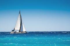 Άσπρη βάρκα που πλέει στην ανοικτή μπλε θάλασσα Στοκ Εικόνα