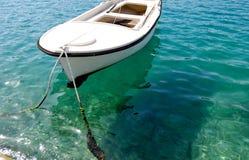 Άσπρη βάρκα σειρών στο κρύσταλλο - σαφή νερά Στοκ Εικόνες