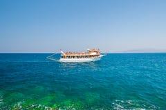 Άσπρη βάρκα, σκάφος, γιοτ, που πλέει με τους τουρίστες κατά μήκος της ακτής στοκ εικόνες