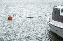 Άσπρη βάρκα στο λιμάνι με τον κόκκινους σημαντήρα και το σχοινί Στοκ Φωτογραφίες
