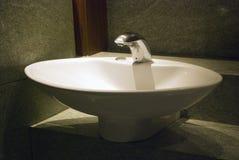 Άσπρη λεκάνη πλυσίματος με τη βρύση και το φωτισμό Στοκ Φωτογραφία