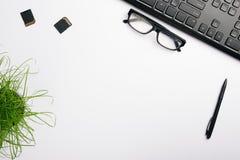 Άσπρη επιφάνεια του πίνακα με το πληκτρολόγιο, τα γυαλιά, τη κάρτα μνήμης και τη μάνδρα Μινιμαλιστικός χώρος εργασίας Υπουργείων  στοκ εικόνες