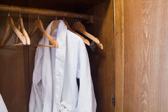 Άσπρη εσθήτα ξενοδοχείων σε μια κρεμάστρα στην ντουλάπα Στοκ Φωτογραφίες
