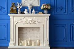 Άσπρη εστία με έναν καθρέφτη στο δωμάτιο, στα ρολόγια ραφιών, αναμνηστικά, κεριά Στοκ Εικόνες