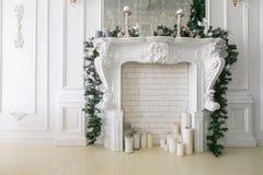 Άσπρη εστία που διακοσμείται με τα κεριά και τους κλάδους έλατου διακοσμημένο Χριστούγεν& Κλασικά διαμερίσματα, πρωί στο ξενοδοχε στοκ φωτογραφίες με δικαίωμα ελεύθερης χρήσης