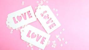 Άσπρη ετικέττα δώρων με την αγάπη επιγραφής σε ένα ρόδινο υπόβαθρο στοκ εικόνα