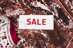Άσπρη ετικέττα υφασμάτων πώλησης στο ύφασμα τσεκιών Αγορές ή έννοια πωλήσεων Στοκ Φωτογραφία