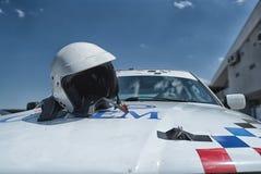 Άσπρη ηλιόλουστη ημέρα αγωνιστικών αυτοκινήτων και κρανών πριν από τη φυλή Στοκ Φωτογραφίες