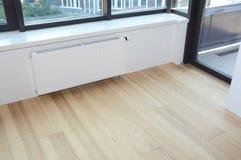 Άσπρη θέρμανση θερμαντικών σωμάτων με τη θερμοστάτη για την ενέργεια - αποταμίευση, ξύλινο πάτωμα στο σύγχρονο κενό δωμάτιο στοκ εικόνες