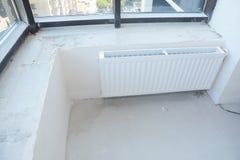 Άσπρη θέρμανση θερμαντικών σωμάτων με τη θερμοστάτη για την ενέργεια - αποταμίευση στο ατελές σύγχρονο κενό επίπεδο δωμάτιο στοκ φωτογραφία