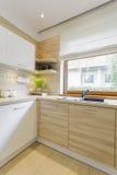 Άσπρη και ξύλινη κουζίνα με τα γραφεία στοκ φωτογραφία