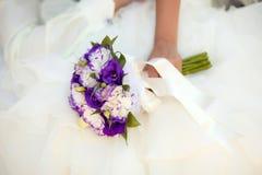 Άσπρη και πορφυρή γαμήλια ανθοδέσμη με τα eustomas στα χέρια Στοκ φωτογραφίες με δικαίωμα ελεύθερης χρήσης
