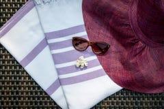 Άσπρη και πορφυρή τουρκική ένας peshtemal χρώματος/μια πετσέτα, γυαλιά ηλίου, άσπρα θαλασσινά κοχύλια και καπέλο αχύρου στον αργό Στοκ Φωτογραφία