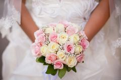 Άσπρη και ρόδινη γαμήλια ανθοδέσμη με τα τριαντάφυλλα στα χέρια της νύφης Στοκ Εικόνες