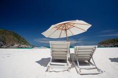 Άσπρη καρέκλα παραλιών στην παραλία άμμου Στοκ Εικόνες