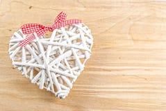 Άσπρη καρδιά που γίνεται από την ιτιά με την κόκκινη κορδέλλα στο ξύλινο υπόβαθρο Στοκ Εικόνα