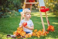 Άσπρη καυκάσια συνεδρίαση κοριτσιών παιδιών παιδιών μικρών παιδιών έξω στο πάρκο θερινού φθινοπώρου με το σχεδιασμό easel που τρώ Στοκ Εικόνες