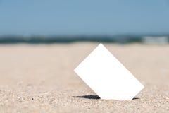 Άσπρη κενή στιγμιαία κάρτα φωτογραφιών στην άμμο παραλιών Στοκ φωτογραφίες με δικαίωμα ελεύθερης χρήσης