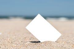 Άσπρη κενή στιγμιαία κάρτα φωτογραφιών στην άμμο παραλιών Στοκ Εικόνες