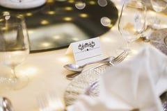 Άσπρη κενή χλεύη ετικετών εγγράφου επάνω με την τέχνη διακοσμήσεων για το όνομα στον πίνακα γευμάτων με το μουτζουρωμένο υπόβαθρο Στοκ εικόνα με δικαίωμα ελεύθερης χρήσης