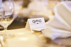Άσπρη κενή χλεύη ετικετών εγγράφου επάνω με την τέχνη διακοσμήσεων για το όνομα στον πίνακα γευμάτων με το μουτζουρωμένο υπόβαθρο Στοκ φωτογραφίες με δικαίωμα ελεύθερης χρήσης