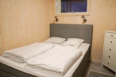 Άσπρη κλινοστρωμνή και comfy μαξιλάρι στο ξύλινο γραφείο στην κρεβατοκάμαρα στοκ εικόνα