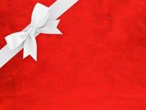 Άσπρη κορδέλλα με το τόξο σε κόκκινο αφηρημένο χαρτί σύστασης σχεδίων Στοκ Φωτογραφία