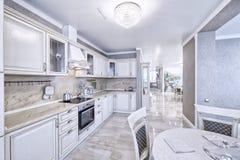 Άσπρη κουζίνα σύγχρονου σχεδίου σε ένα ευρύχωρο διαμέρισμα Στοκ φωτογραφία με δικαίωμα ελεύθερης χρήσης
