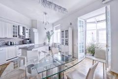 Άσπρη κουζίνα σύγχρονου σχεδίου σε ένα ευρύχωρο διαμέρισμα Στοκ Εικόνες