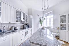 Άσπρη κουζίνα σύγχρονου σχεδίου σε ένα ευρύχωρο διαμέρισμα Στοκ εικόνα με δικαίωμα ελεύθερης χρήσης