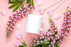 Άσπρη κούπα καφέ με τα λουλούδια και τις καρδιές lupine στο ρόδινο backgrou Στοκ φωτογραφία με δικαίωμα ελεύθερης χρήσης
