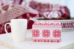Άσπρη κούπα με ένα δώρο στον πίνακα στο νέο έτος στοκ εικόνες